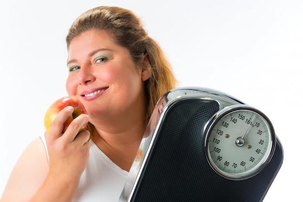 Otyła kobieta ze skalą pod pachą i jabłkiem Premium Zdjęcia