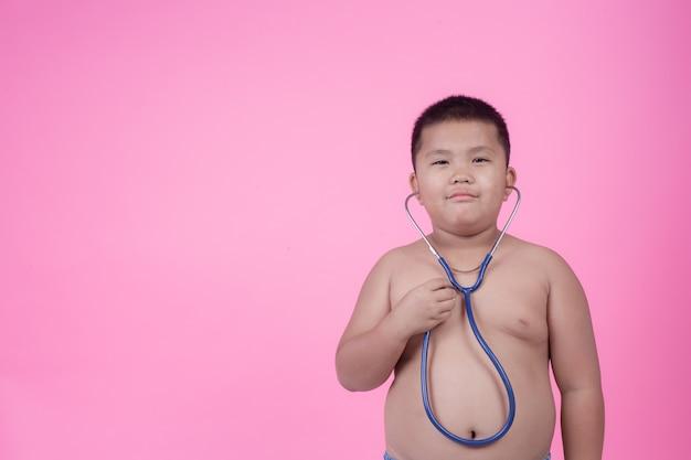 Otyły chłopiec z nadwagą na różowym tle. Darmowe Zdjęcia