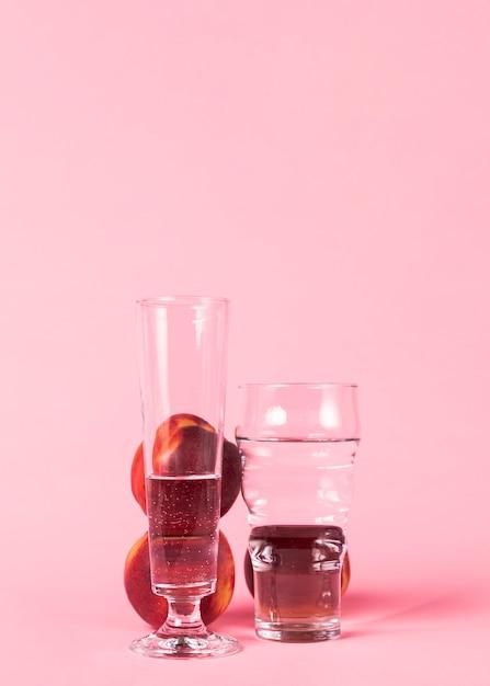 Owoc nektaryny i szklanki wypełnione wodą Darmowe Zdjęcia