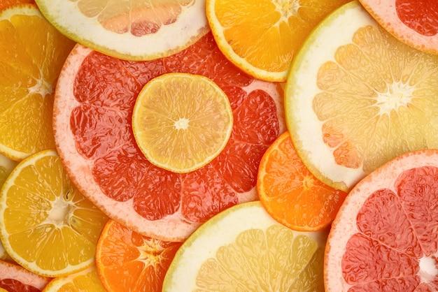 Owoce Cytrusowe Pokrojone W Okrągłe Kawałki: Pomarańcza, Grejpfrut, Cytryna, Mandarynka. Dojrzałe I Soczyste Owoce, Widok Z Góry Premium Zdjęcia