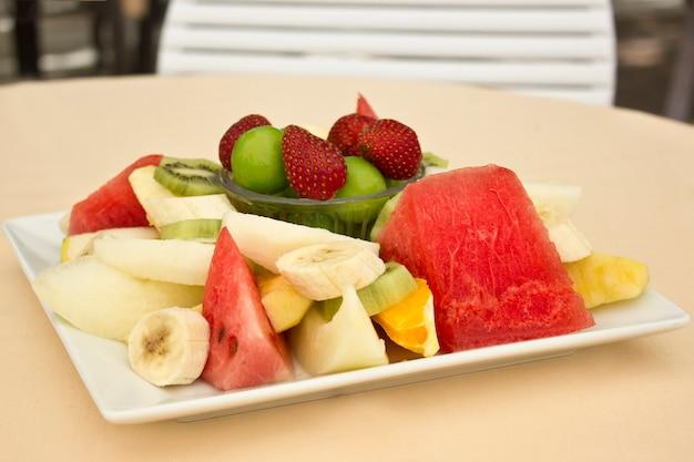 Owoce Na Talerzu. Zielona śliwka, Truskawka, Banan, Kiwi, Arbuz, Pomarańcza I Jabłko. Premium Zdjęcia