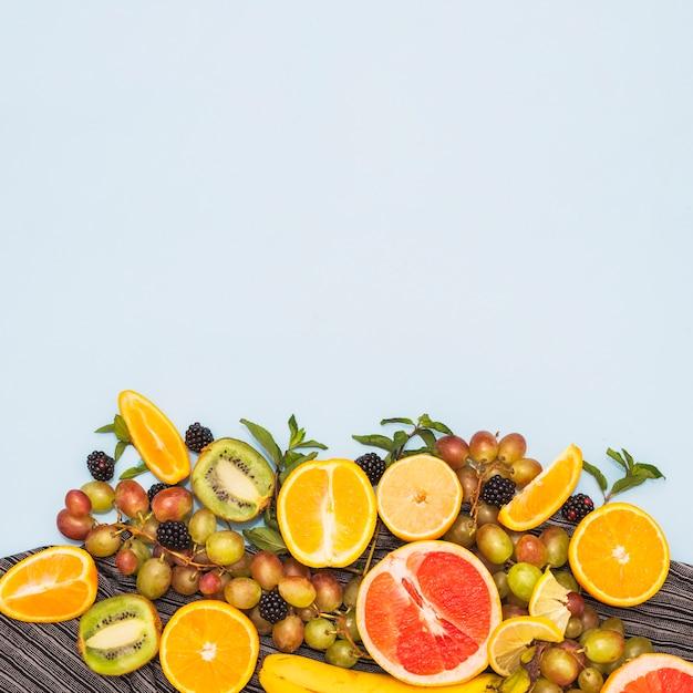 Owoce po połowie; winogrona i jeżyny na niebieskim tle Darmowe Zdjęcia