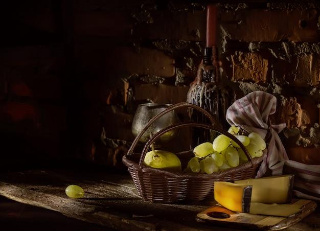 Owoce w koszu i butelkę ze świecą w butelce wina Premium Zdjęcia