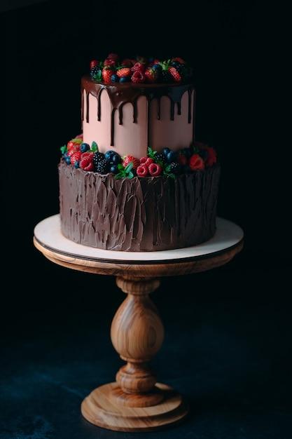 Owocowy czekoladowy tort na drewnianym stojaku na czerni. Premium Zdjęcia
