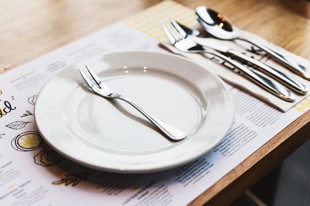 Oyster Widelec Z Sztućcami: łyżka, Widelec I Nóż Na Białym Talerzu Ceramicznym. Posrebrzane Artykuły Spożywcze. Premium Zdjęcia