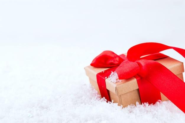 Ozdobne Brązowe Pudełko Z Dużą Czerwoną Kokardą Stojącą W świeżym śniegu Premium Zdjęcia