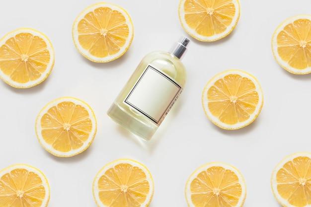 Pachnący Olejem Lub Perfumami, Na Białej ścianie, Ozdobiony Wzorami Plasterków Cytryny. Pojęcie Aromaterapii Lub Pielęgnacji Ciała, Zapachy Cytrusowe. Premium Zdjęcia