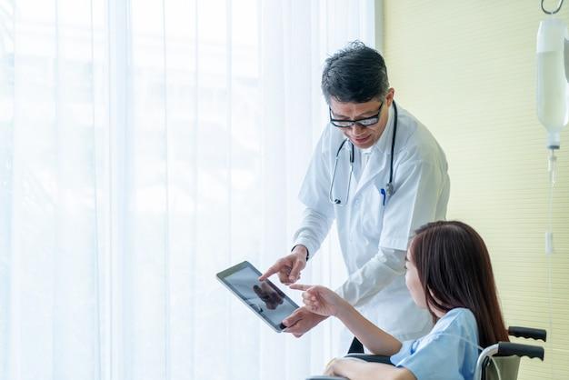 Pacjentki Na Wózku Inwalidzkim Z Starszy Lekarz Premium Zdjęcia