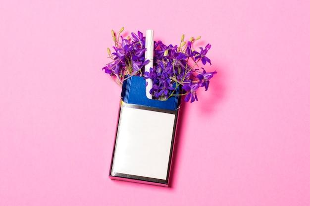 Paczka papierosów na różowym tle w paczce niebieskich kwiatów Premium Zdjęcia