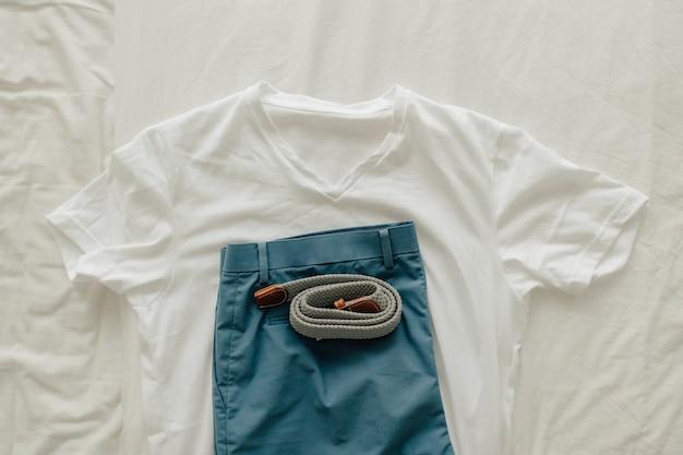 Paczka Ubrań Na łóżku Z Białą Niebieską Koszulką Krótką I Paskiem Do Ubrania. Premium Zdjęcia