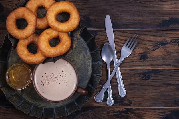 Pączki I Dżem Z Filiżanki Kawy Na Drewnianym Stole. Słodkie Niezdrowe śniadanie Premium Zdjęcia