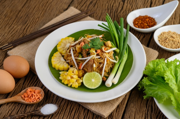 Pad Thai W Białym Talerzu Z Cytryną, Jajkami I Przyprawami Na Drewnianym Stole. Darmowe Zdjęcia
