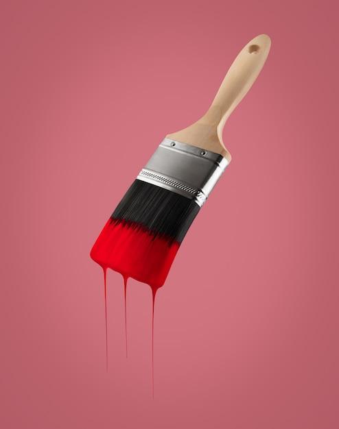 Paintbrush ładował Z Czerwonym Kolorem Kapiącym Z Szczecina - Odizolowywającego Na Czerwonym Tle. Premium Zdjęcia