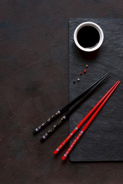 Pałeczki i miska z sosem sojowym na czarnym tle kamienia Premium Zdjęcia