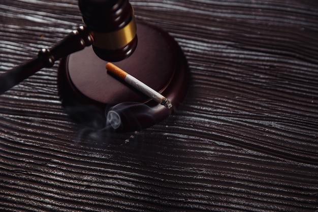 Palenie Papierosów I Drewniany Młotek Sędziego Na Stole. Premium Zdjęcia