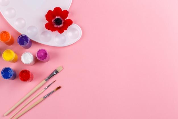 Paleta akwarela i pędzle na różowym tle Premium Zdjęcia