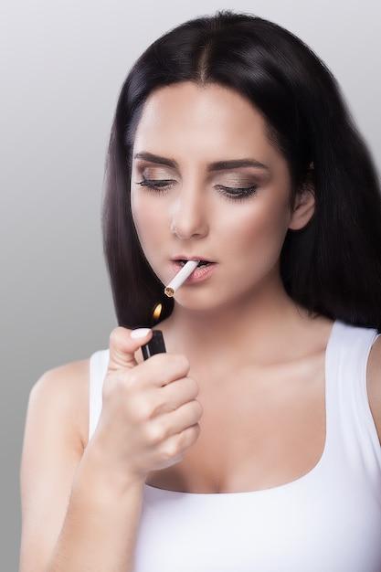 Palić. młoda dziewczyna zapala papierosa, trzymając ją w ustach. zakaz palenia Premium Zdjęcia