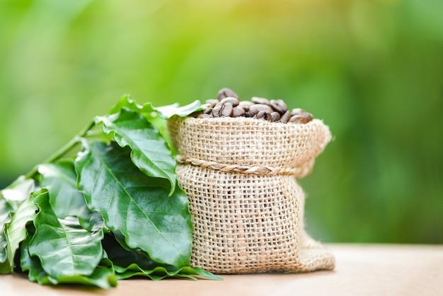 Palona kawa w worku z zielonym liściem na drewnianym stole i zieleni Premium Zdjęcia