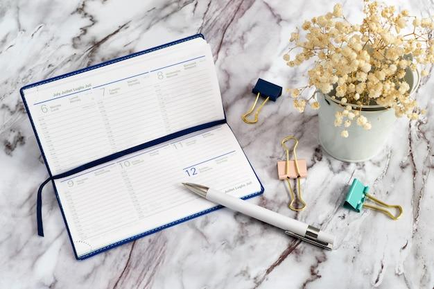 Pamiętnik z białym długopisem i spinaczami na marmurowym stole i białymi kwiatami. notatnik na dokumenty biznesowe na tydzień. Premium Zdjęcia