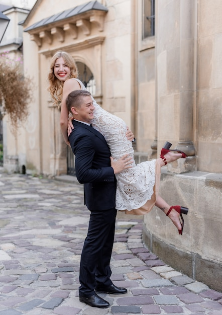 Pan Młody Nosi Pannę Młodą Na Ramieniu, Szczęśliwa Para, Dzień ślubu, Na Zewnątrz Darmowe Zdjęcia