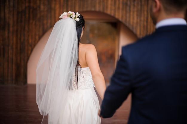 Pan młody w garniturze podążający za swoją piękną narzeczoną ubrany w białą sukienkę Premium Zdjęcia