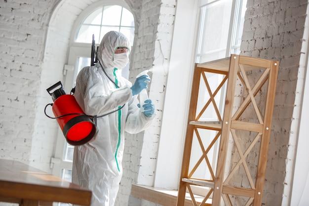 Pandemia Wirusa Koronawirusa. środek Dezynfekujący W Kombinezonie Ochronnym I Masce Rozpyla środki Dezynfekujące W Pomieszczeniu. Darmowe Zdjęcia