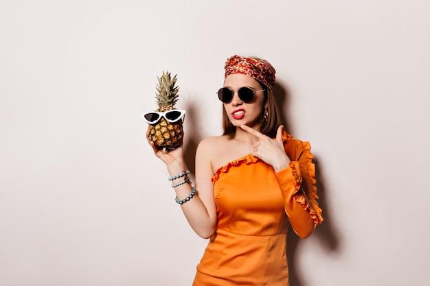 Pani W Pomarańczowej Sukience I Okularach Przeciwsłonecznych Pozuje W Zamyśleniu I Trzyma Ananasa Na Odizolowanej Przestrzeni. Darmowe Zdjęcia