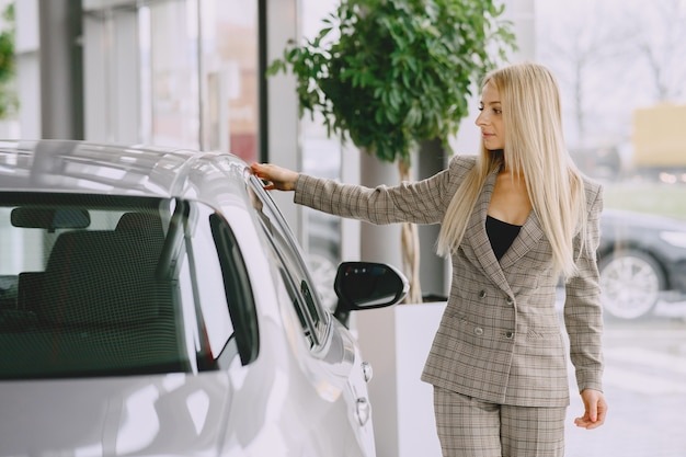 Pani W Salonie Samochodowym. Kobieta Kupuje Samochód. Elegancka Kobieta W Brązowym Garniturze. Darmowe Zdjęcia