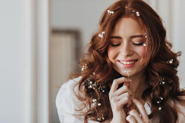 Pani Z Kwiatami W Czerwonych Lokach Z Uśmiechem Pozowanie. Kryty Portret Kobiety Z Małą Rośliną W Dłoniach. Darmowe Zdjęcia