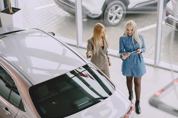 Panie W Salonie Samochodowym. Kobieta Kupuje Samochód. Elegancka Kobieta W Niebieskiej Sukience. Menedżer Pomaga Klientowi. Darmowe Zdjęcia