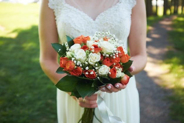 Panna Młoda Trzyma Bukiet Pomarańczowych Róż Premium Zdjęcia