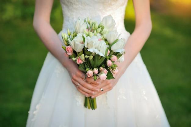 Panna młoda trzyma piękny biały bukiet ślubny Premium Zdjęcia