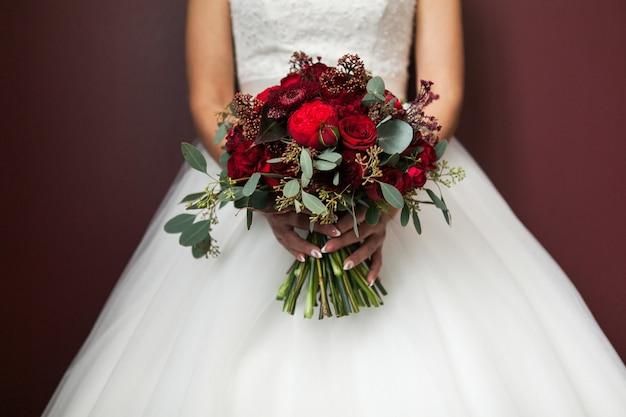Panna młoda w białej eleganckiej sukni ślubnej trzyma bukiet ślubny. Premium Zdjęcia
