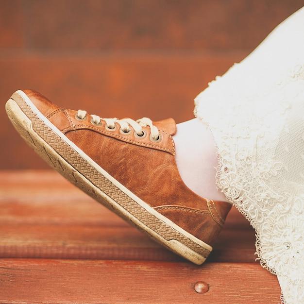 Panna młoda w białej sukni ślubnej i brązowych trampkach lub butach sportowych. kobieca stopa w tenisówce, na drewnianej ławce pomalowanej, zbliżenie Premium Zdjęcia