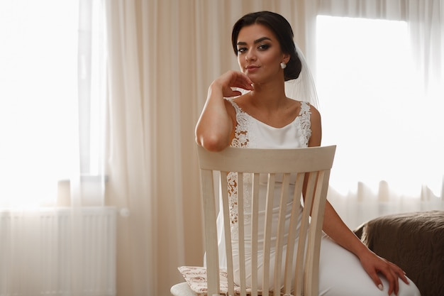 Panna młoda w stylowej sukience i długim welonie na krześle wewnątrz Premium Zdjęcia
