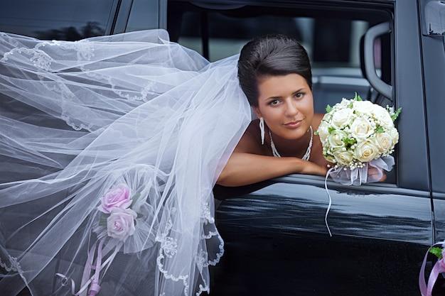 Panna młoda z trzepoczącym welonem wygląda z okna samochodu Premium Zdjęcia