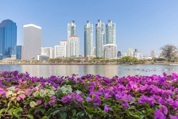 Panoramiczny Widok Na Wieżowce Miasta Przez Różowe Kwiaty I Duże Jezioro Premium Zdjęcia