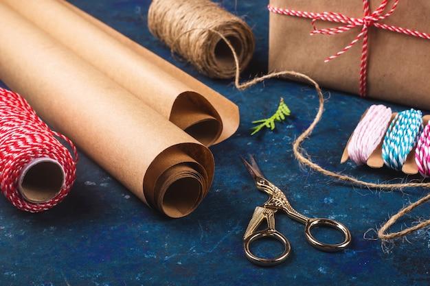 Papier Pakowy Do Pakowania Prezentów Obok Nożyczek I Różnych Lin. Przygotuj Się Na świąteczny Koncept. Premium Zdjęcia