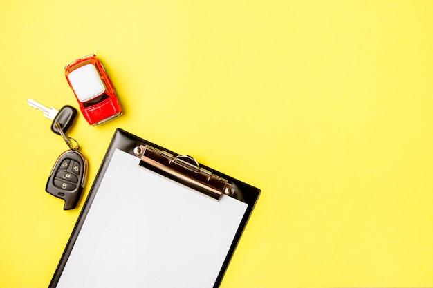 Papier puste z zabawkami czerwony samochód i klucze na żółtym tle. kontrola techniczna lub kredyt samochodowy. Premium Zdjęcia