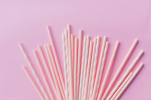 Papierowa słoma w pastelowych kolorach na różowo. wiele słomek koktajlowych w różowe paski Premium Zdjęcia