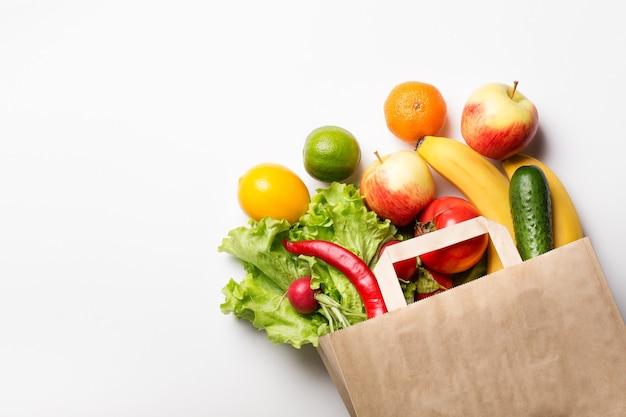 Papierowa Torba Z Warzywami I Owocami Na Białym Tle. Zamawianie Online W Sklepie Spożywczym. Pojęcie Prawidłowego Odżywiania. Dostawa Jedzenia. Premium Zdjęcia