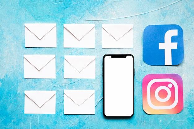 Papierowe Białe Kopertowe Wiadomości I Ogólnospołeczna Medialna Ikona Z Telefonem Komórkowym Na Błękitnym Tle Darmowe Zdjęcia
