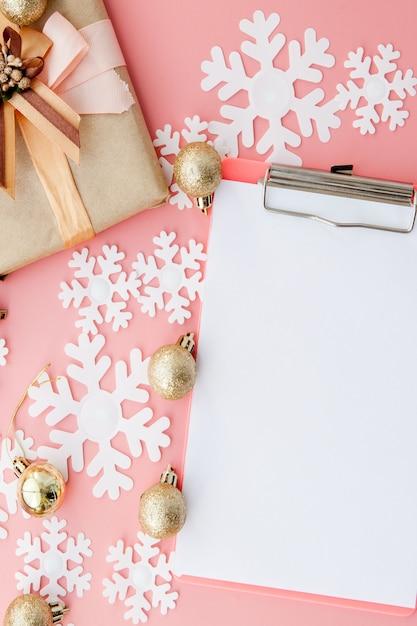 Papierowe płatki śniegu, folder i złote kulki na różowym tle Premium Zdjęcia
