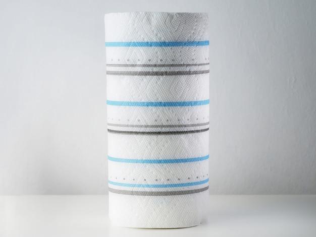 Papierowe Ręczniki Zwijają Się Z Niebieskimi Paskami Na Białym Stole. Premium Zdjęcia