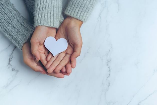 Papierowe Serce W Dłoniach Pary Na Marmurowym Stole Darmowe Zdjęcia