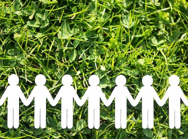 Papierowi ludzie na zielonej trawy tle Premium Zdjęcia