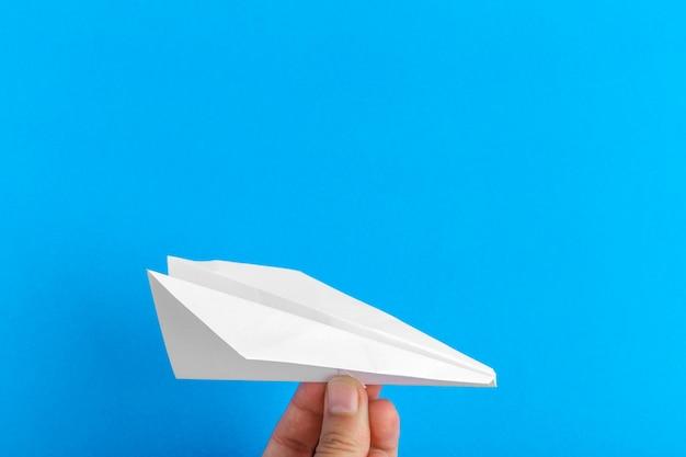 Papierowy samolot na jaskrawym tle trzyma w ludzkiej ręce. koncepcja podróży i turystyki Premium Zdjęcia