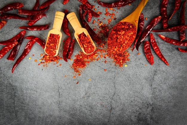 Papryka Cayenne Na Przyprawach Drewnianą łyżką I Suszoną Papryczką Chilli, Grupa Gorącego Chili W Proszku Na Czarnej Płycie Widok Z Góry Składniki Stół Azjatyckie Jedzenie Pikantne W Tajlandii Premium Zdjęcia