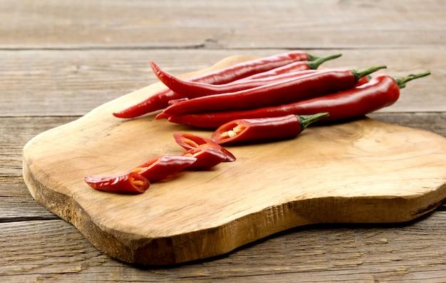 Papryki Gorący Chili Strąki Na Drewnianej Desce. Premium Zdjęcia