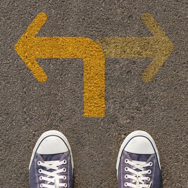 Para butów stojących na drodze z dwukierunkowa żółta strzałka Premium Zdjęcia